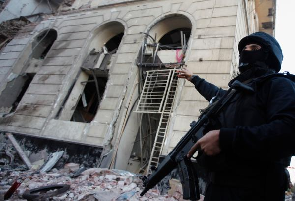 A riot police officer gestures outside building of Directorate of Security after explosion in Egypt's Nile Delta town of Dakahlyia